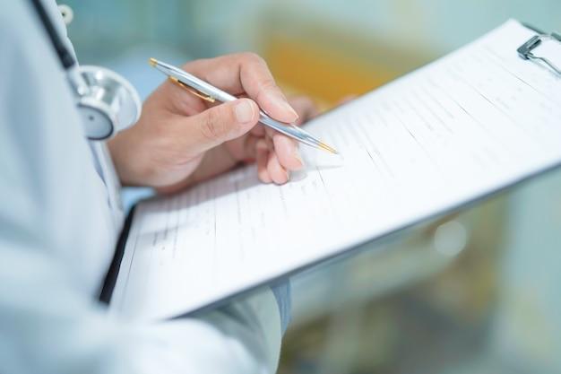O doutor escreve abaixo o diagnóstico na prancheta no hospital.