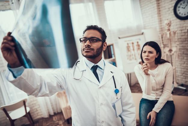 O doutor está olhando o raio x da mulher.