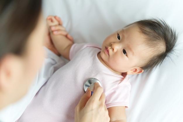 O doutor fêmea está escutando a taxa de pulso do coração do bebê recém-nascido asiático que sorri na cama usando o estetoscópio na sala.