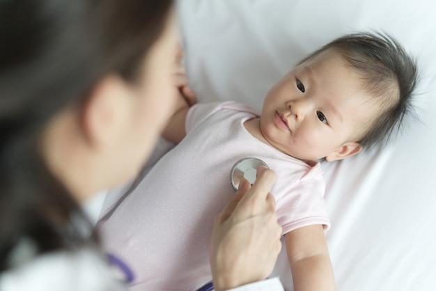 O doutor fêmea está escutando a taxa de pulso do coração do bebê recém-nascido asiático que sorri na cama usando o estetoscópio.
