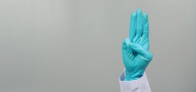 O doutor mão usa luva de látex. um sinal de mão de 3 dedos aponta para cima, significando três, terceiro ou use em protesto. é colocado em um fundo cinza.