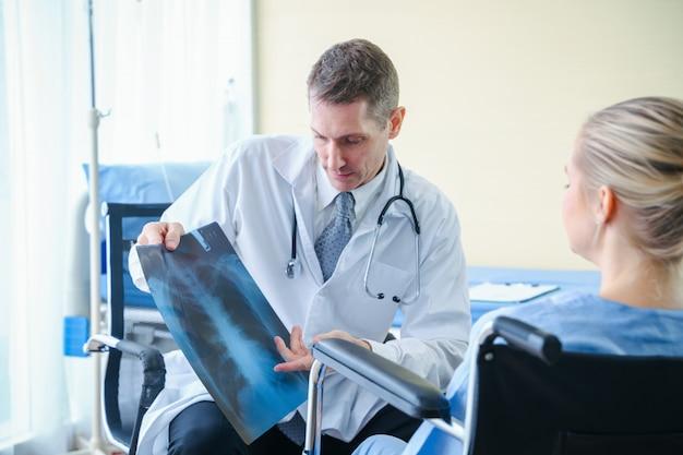 O doutor mostra e explica no resultado de raio x ao paciente na clínica.