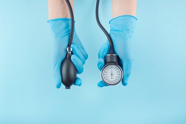 O doutor prende em suas mãos um dispositivo médico para medir a pressão sanguínea em um fundo azul. fundo médico. o remédio. copie o espaço.