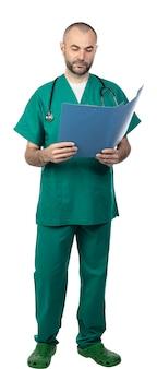 O doutor que está com uniforme verde lê a prancheta em um dobrador azul.