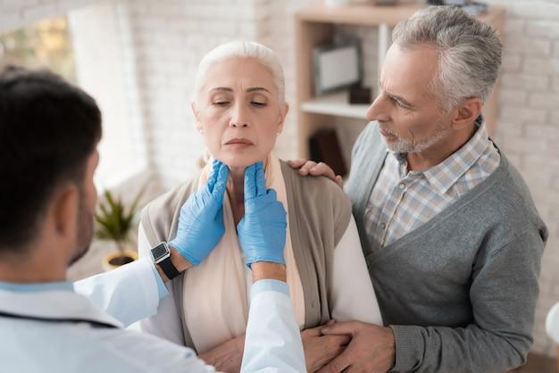 O doutor verifica os gânglios linfáticos da mulher idosa.