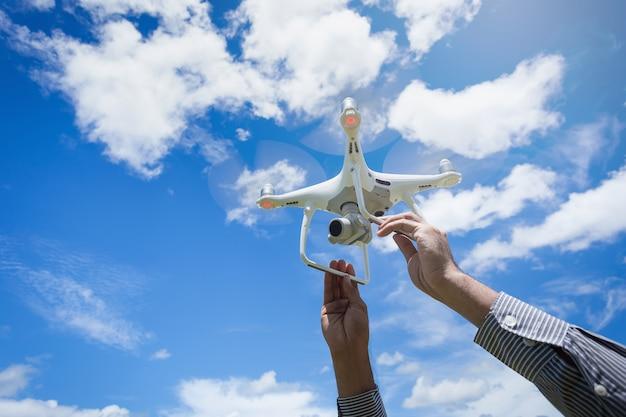 O drone e fotógrafo homem mãos o drone com a câmera profissional