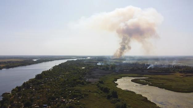 O drone sobrevoa um rio ondulante de cor azul cercado por uma vila local com vários edifícios e um pantanal