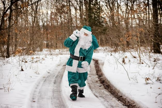 O duende de natal em um terno verde traz uma caminhada pela floresta de inverno carregando os presentes de natal de ano novo e olhando para longe