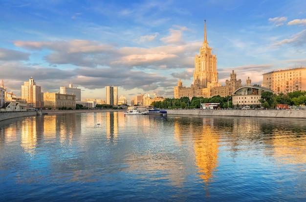 O edifício do antigo hotel ucrânia com reflexo no rio moscou