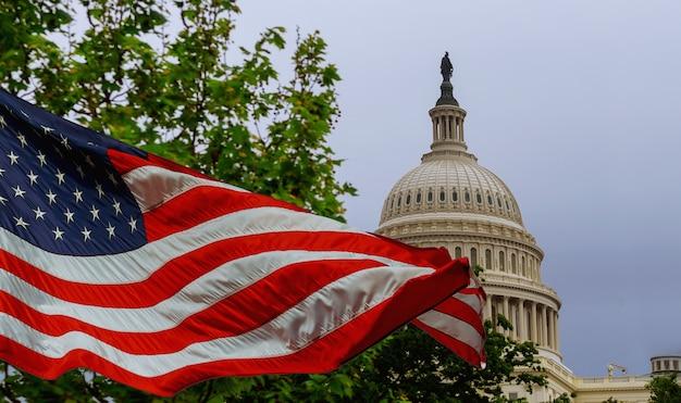 O edifício do capitólio dos eua com uma bandeira americana acenando sobreposta ao céu