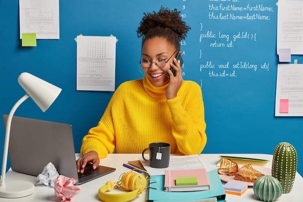 O editor profissional da web cria a estrutura técnica do site, discute alguns problemas de trabalho via smartphone, usa óculos, navega na internet em um laptop moderno.