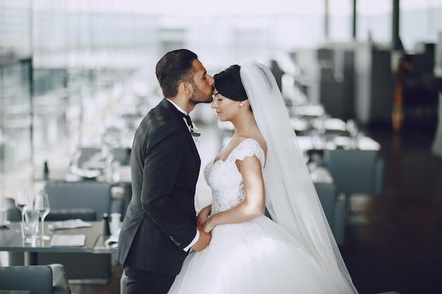O elegante e elegante noivo e sua linda esposa em um restaurante