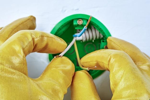 O eletricista com luvas de proteção está montando o interruptor ou a caixa redonda elétrica na parede da tomada.