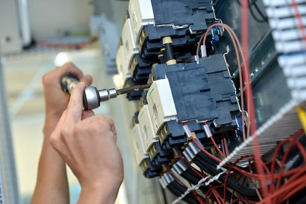 O eletricista está conectando o fio do cabo elétrico. manutenção do engenheiro e conserto do controle do sistema.