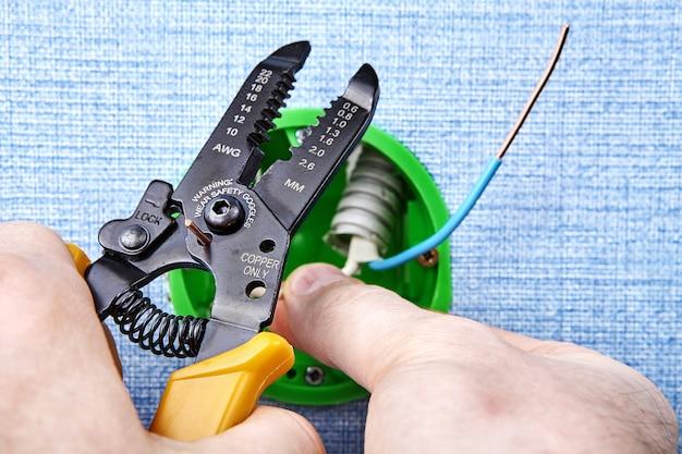 O eletricista está cortando a extremidade do fio de cobre com um cortador removedor durante a montagem da caixa de tomada redonda.