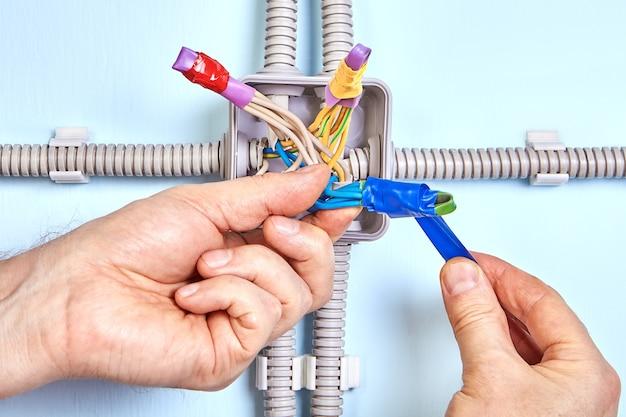 O eletricista está enrolando fita nas pontas dos fios em um tubo retrátil durante a manutenção elétrica.
