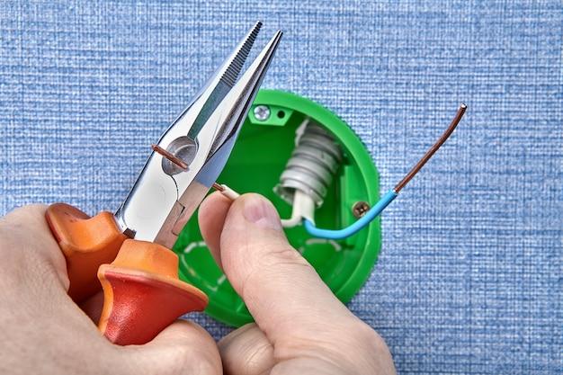 O eletricista está montando uma nova caixa elétrica redonda cortando a fiação de cobre com um alicate elétrico, trabalho elétrico.