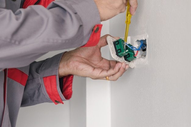 O eletricista está usando uma chave de fenda para verificar o plugue de energia na parede.
