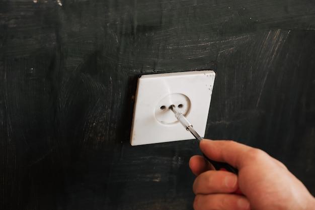 O eletricista masculino altera uma tomada elétrica antiga desaparafusando o parafuso com uma chave de fenda
