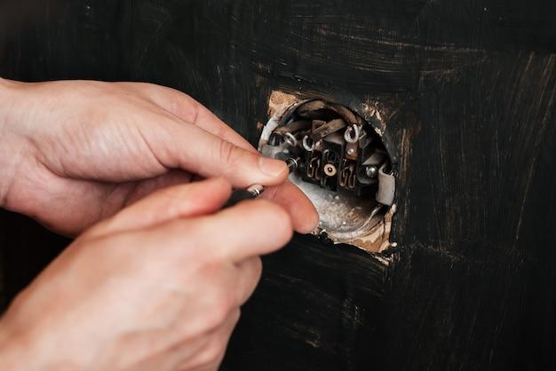 O eletricista masculino repara uma tomada elétrica defeituosa velha com uma chave de fenda