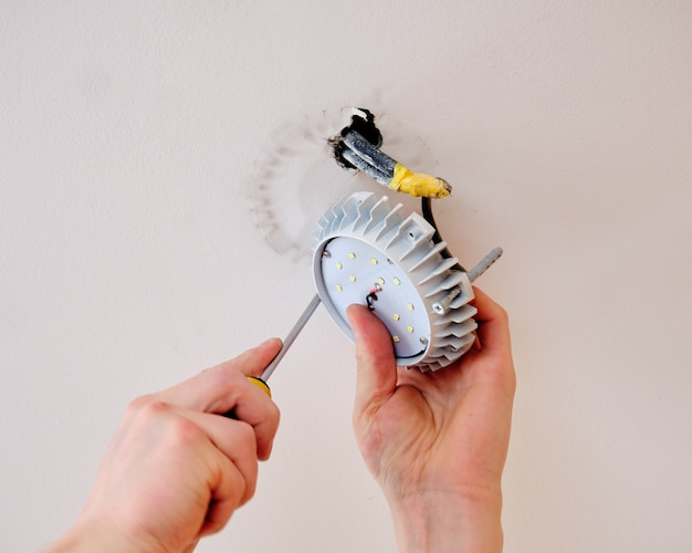 O eletricista monta a lâmpada no teto com uma chave de fenda