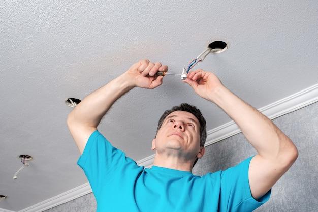 O eletricista prepara os cabos antes de instalar os refletores de led
