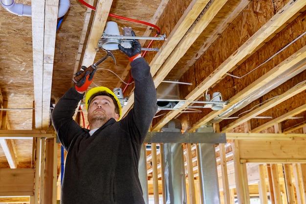O eletricista que prega na lâmpada do teto instala a lâmpada de iluminação