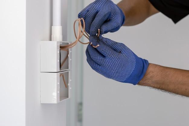 O eletricista usa luvas azuis, está usando uma faca de cortador de cabo elétrico para instalar o plugue