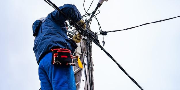 O eletricista vysotnik faz instalação de redes elétricas