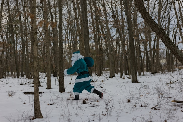 O elfo de terno verde traz presentes de ano novo caminhando pela floresta de inverno