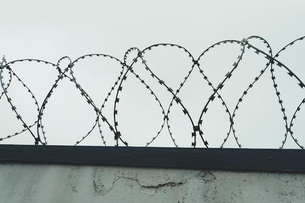 O emaranhado de farpa com céu cinza. a cerca da prisão. holocausto.
