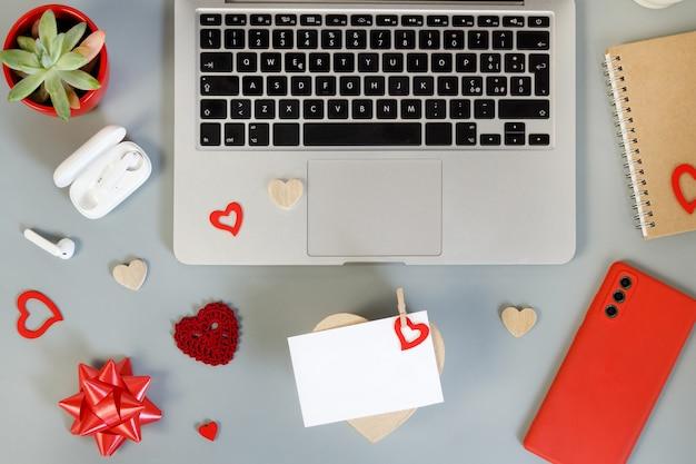 O embrulho do dia dos namorados apresenta-se perto de dispositivos modernos na vista superior de mesa cinza. conceito de dia dos namorados