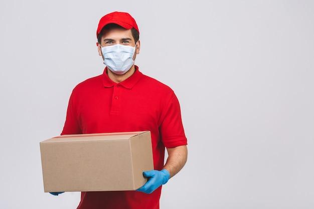 O empregado do homem de entrega nas luvas uniformes da máscara protetora do t-shirt vermelho do espaço em branco da tampa mantém a caixa de papelão vazia isolada na parede branca. serviço conceito de vírus de coronavírus pandêmico de quarentena 2019-ncov.