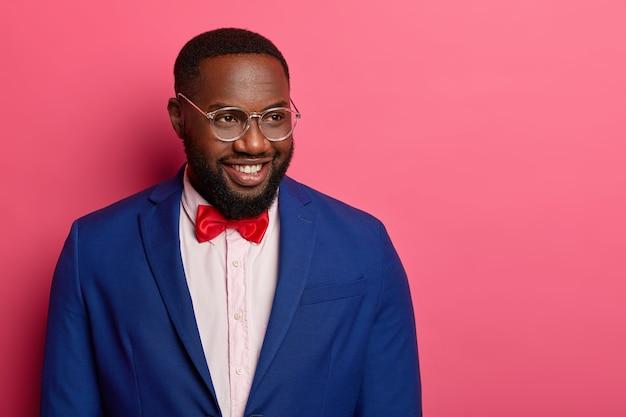 O empregador confiante do sexo masculino sorri alegremente enquanto encontra os colegas, usa óculos óticos e terno formal, isolado sobre o espaço rosa