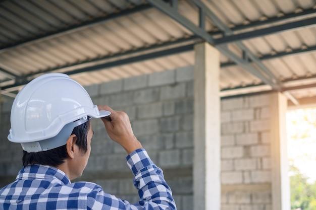 O empreiteiro ficou olhando o canteiro de obras ou o prédio que está sendo reformado ou modificado. verifique a prontidão da construção.