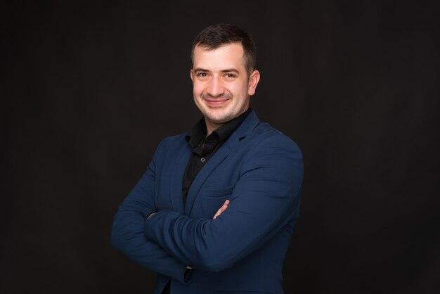 O empresário alegre de terno azul está de pé com as mãos cruzadas e sorrindo em fundo preto.