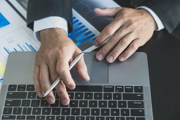 O empresário analisa o gráfico de finanças com o laptop no escritório para definir metas de negócios de gerenciamento desafiadoras e planejar para atingir a nova meta