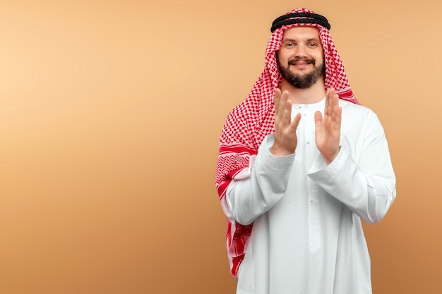 O empresário árabe com roupas nacionais está aplaudindo. copie o espaço.