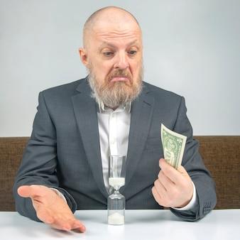 O empresário barbudo recebe um pequeno pagamento por trabalhar com dinheiro contra a ampulheta. conceito de valor do tempo para pagar pelo negócio