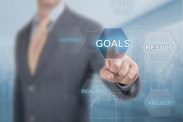 O empresário clica no botão do gol na tela virtual. atingir objetivos no conceito de negócio. conceito de alcançar objetivos de negócios. execução do plano de negócios. conceito sobre objetivos e sucesso