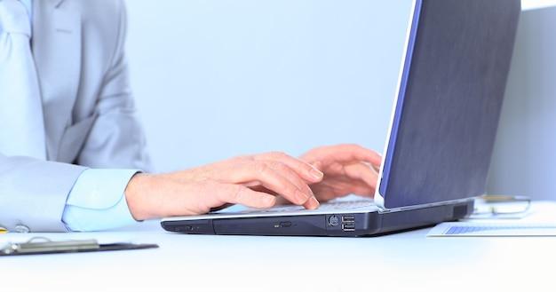 O empresário com a idade trabalha para o laptop. isolado em um fundo branco.