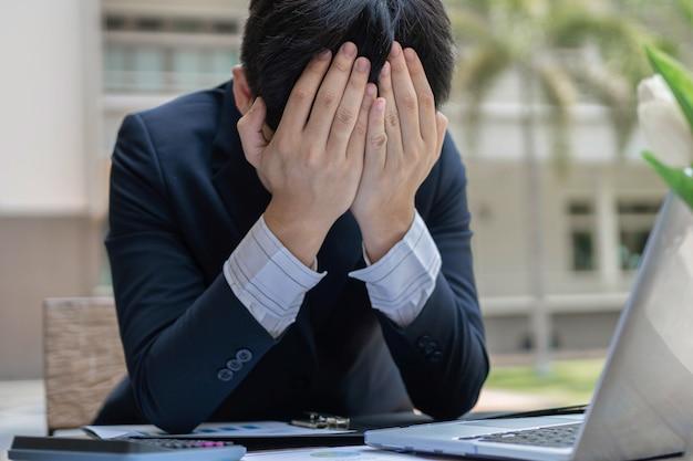 O empresário concebe os empresários usando as duas mãos cobrindo a testa, sentindo-se desesperado por encontrar o maior problema.