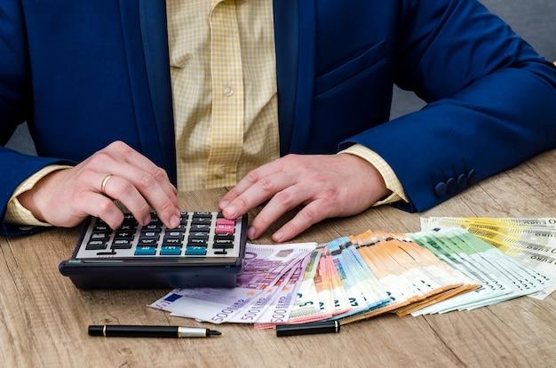 O empresário conta euros usando uma calculadora