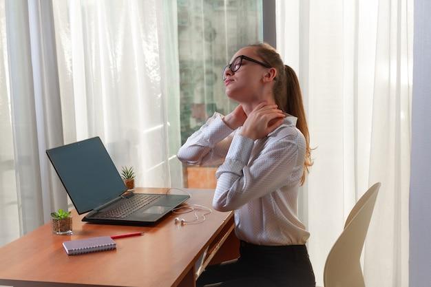 O empresário de óculos está sentindo dores nos músculos do pescoço e massageando o local do desconforto. trabalho sedentário. necessidade de descanso
