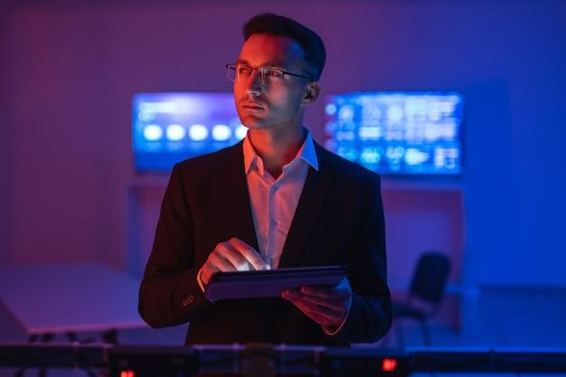 O empresário de óculos trabalhando com um tablet