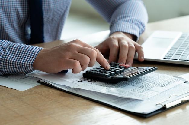 O empresário de planejamento de dedução de impostos que calcula o saldo do negócio em uma calculadora está preparando um corte de impostos