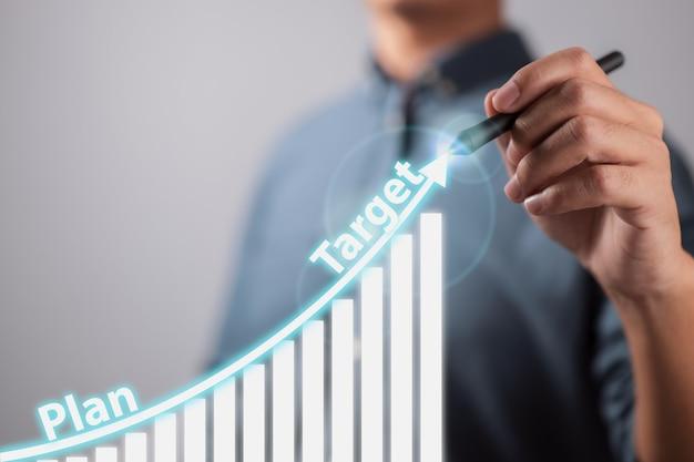 O empresário desenha uma seta de tendência crescente e um gráfico crescente do plano ao objetivo