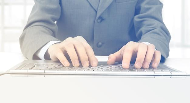 O empresário digitando em seu laptop no escritório