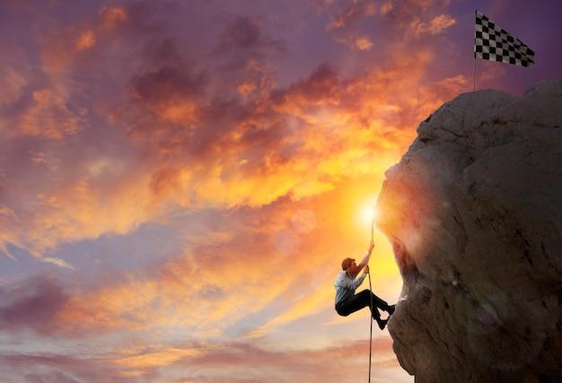 O empresário escala uma montanha para pegar a bandeira. objetivo de negócios de realização e conceito de carreira difícil