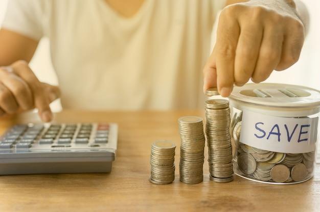 O empresário está colocando moedas na coluna empilhadas e acumuladas que representam economia de dinheiro ou ideia de planejamento financeiro para a economia.
